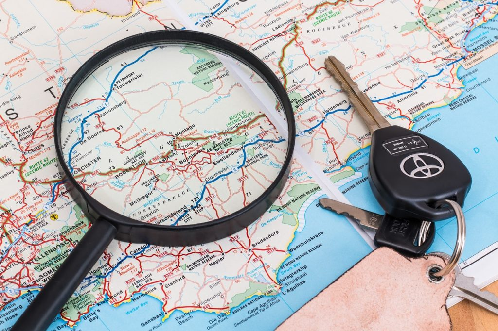 Magnifying glass and set of keys on top of map