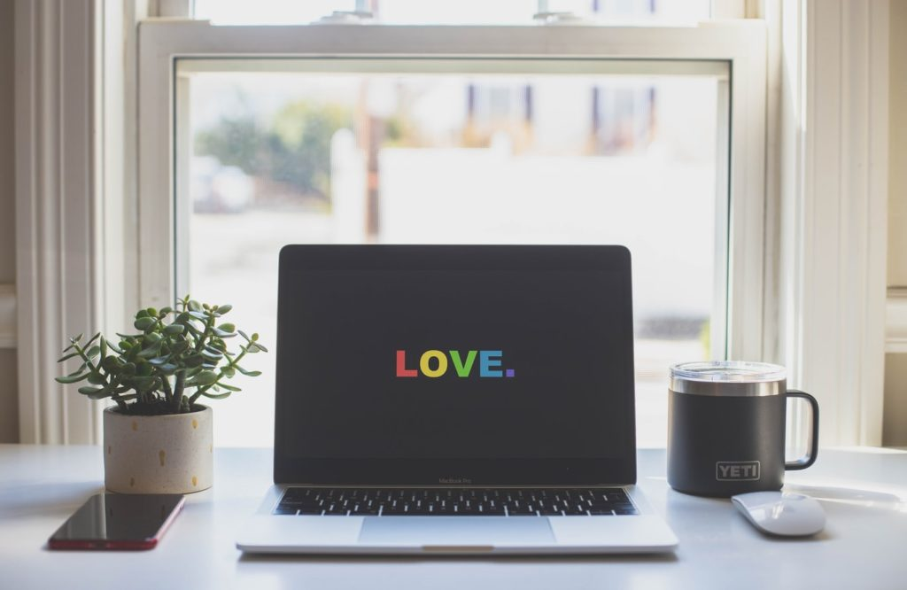 Laptop in front of window on desk with love in rainbow color